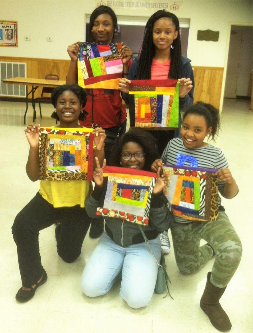 Five young ladies, part of Lillie Fowler Singleton's youth group, pose for a photo with their quilting creations.