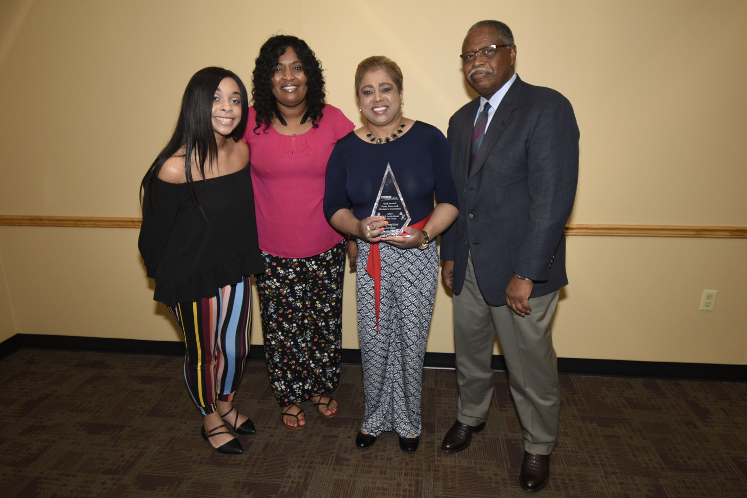 Millicent Price (second from left), FVSU Extension agent for Crawford County and Dr. Mark Latimore Jr. (far right) present Earnestine Jordan (holding trophy) with the 2019 FACS Individual of the Year Award.