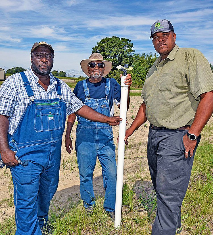 Stefan Price (left), FVSU area Extension agent, poses with Scott (far right) and his father Roland on their farm in Tattnall County.